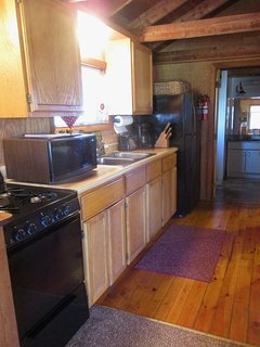 Fully equipped kitchen with stove, microwave, coffee maker, pots, pans, dishes, glasses, utensils..
