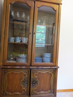 China cabinet. nice plates. wine glasses.