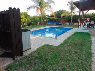 Outside shower, swimming pool, sunbeds in front of the small green yard on the back.