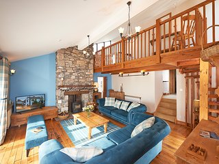 High spacious lounge with wood burning stove, spiral staircase and mezzanine above