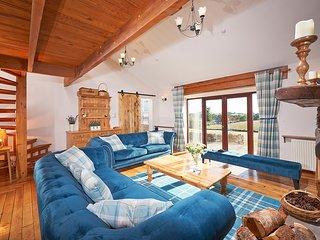 Lounge has patio doors to garden, view over hillsides, solid maple flooring and sliding barn door