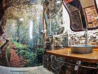 baño, con fotografia en paredes de marcos y cordero, suelo en piedra y paredes en piedra natural