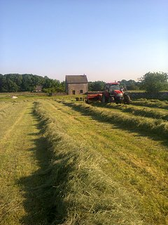 Baling hay in the meadow next to the barn
