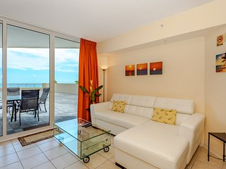 Ocean views from a spacious living room with leather couch, cable TV, and dining room with 4 chairs