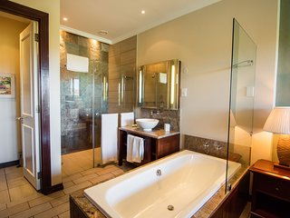 Main bedroom walk-in shower, bath and vanity basin.