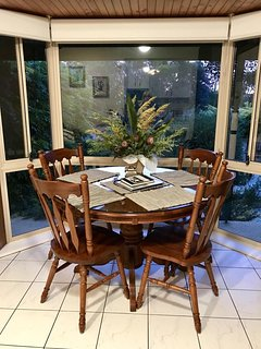 large dining table set in bay window overlooking garden area