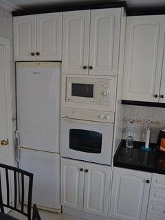 Nevera con congelador, horno y microondas.