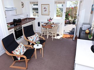 Kitchen area, hob, oven, fridge, sink all pots pans china and cutlery. view to courtyard