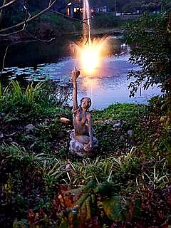 Mermaid and lighted fountain in pond
