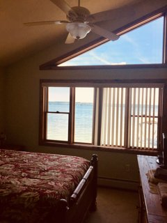 master bedroom queen overlooking lake with dresser, night stands, and ceiling fan. What a view!