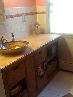 ensuite master bathroom with vessel sink, custom oak vanity and walk in shower