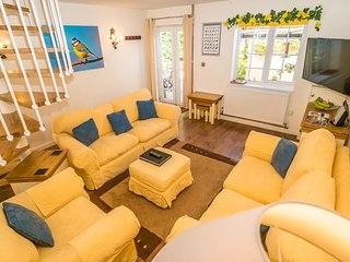 The living area is open plan with a large smart TV. The sofas can sit 6 people. A cupboard is full o