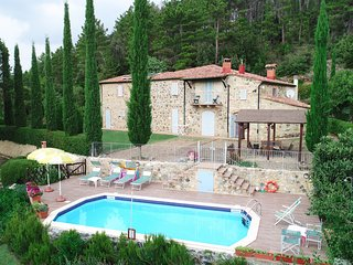 Frontview of Tuscany villa le Capanne: the pool, the cypresses and the lawn