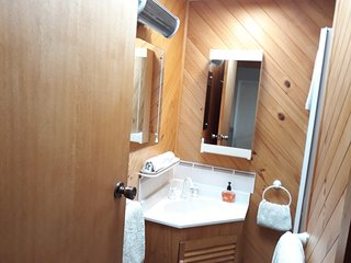 A shower, skylight and wall heater. Separate toilet has a washbasin and mirror.