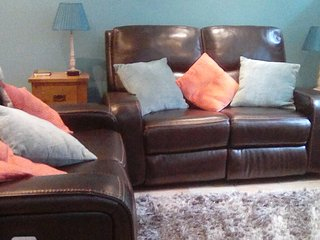 Comfortable seating area with reclining leather sofas.