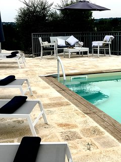 Stylish external seating areas beside the pool and to the rear of the villa.