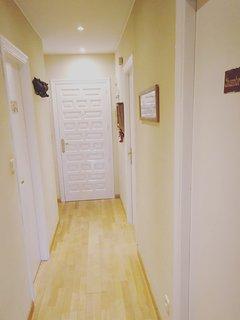 Pasillo amplio que reparte a las habitaciones y baño. Puerta principal de entrada al fondo.