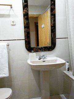 Amplísimo baño con bañera y lavadora de carga superior. Mueble auxiliar a la derecha y luz LED.