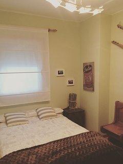 Dormitorio amplio con cama de matrimonio y armario empotrado con mueble auxiliar. Luz natural.