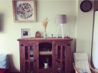 Vista parcial del salón con mueble auxiliar y detalles decorativos que dan calidez a la casa.