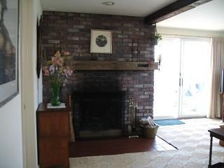 Sala de estar con chimenea y puerta corrediza de vidrio. El agua está a solo 5-6 'de distancia cuando sube la marea.
