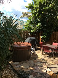 Private patio with hot tub, sitting area, gas grill