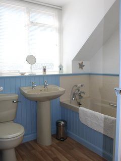 The bright upstairs bedroom with bath and shower attachment.