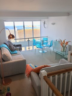 Beautiful lounge area with dining for four, overlooking Fistral and the Headland hotel