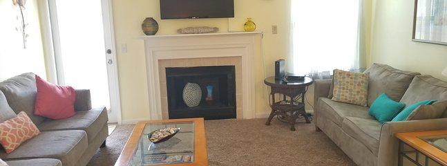 Living room with flat screen TV and soft yellow decor
