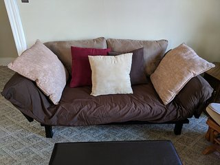 Futon loveseat that converts into a lounge or single bed.
