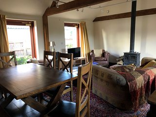 The living room with a wood burning stove and dining area