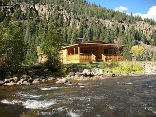 Cozy waterfront cabin w/ mountain views, a wood stove, & a private hot tub
