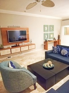 Spacious dining and living room area, with a 55 inch 4K Smart TV and BlueRay player