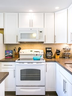 Remodeled kitchen is bright and airy with higher ceiling and undercabinet lights