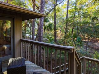 Chill on the back porch which overlooks the surrounding trees and tidal inlet below.