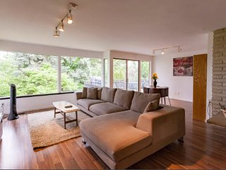 Living room with access to the sundeck. Large sectional couch and informal dining room.