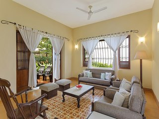 Brightly lit spacious living area with painted tiles and large windows overlooking the garden