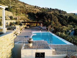 Stone built villa with a windmill and a swimming pool on the island of Kea