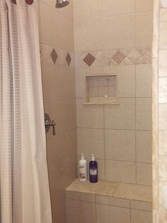 Four Seasons custom tile shower has smooth river rock floor and a bench.