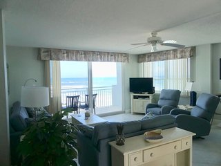 Living room with balcony and sea in the background.  There's a TV with cable.  Internet is provided.