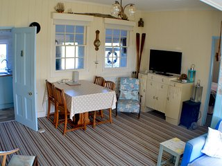 Living room with door to kitchen and hall on left. Door to bedroom 1 on right.