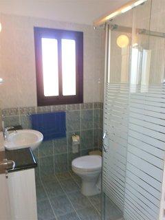 Master en-suite shower room with vanity unit for storage.