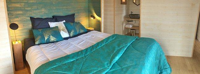 le lit king size et l'accès à l'îlot central de la douche