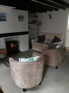 Cosy fireplace, sofa and tub chairs in lounge