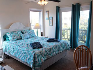 Queen-size bed with desk and two nightstands. Light-blocking drapes cover sliding doors to deck.