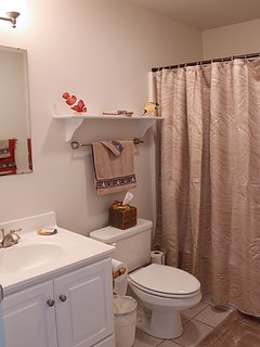 Bathroom has tile tub and shower, with plenty of towels. Shampoo and conditioner included.