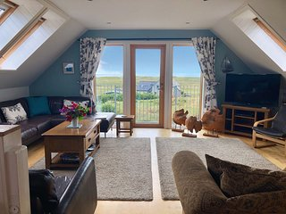Living room and balcony looking out over the community of Kilchattan to the Atlantic