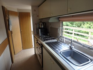 Fitted kitchen with gas hob/oven, fridge, and microwave.