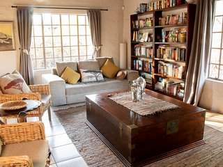 Main Lounge with Library leading to pool and open braai area.