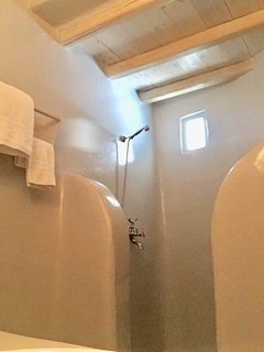 The spacious Mykonian-style shower in the bathroom of the second bedroom has just been renovated.
